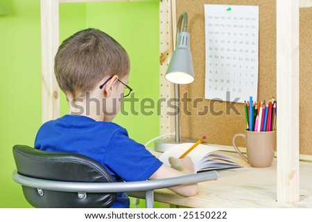 7 years old boy doing his homework - education - stock photo