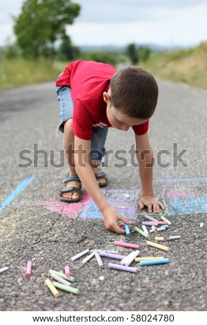 8 years old boy drawing with sidewalk chalk - family and kids - stock photo