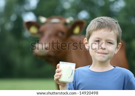 6-7 years old boy drinking milk on farm - stock photo