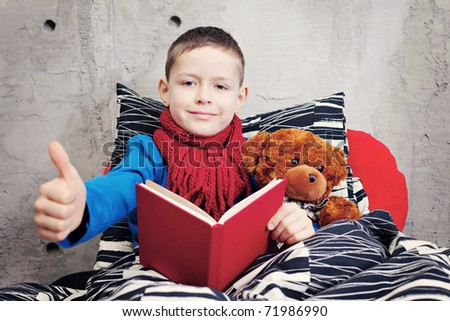 9 years old boy ill reading book in bed - kids and family - stock photo