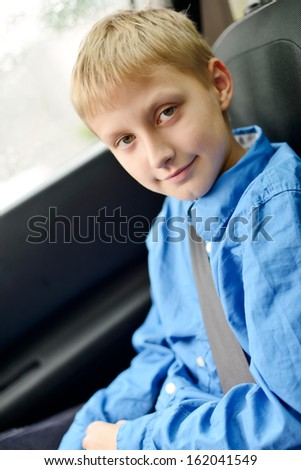 10 years old boy in car with belt - stock photo