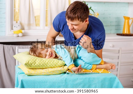 2-3 years old boy lays on a pillows and his father stands next to him. Boy is dressed in a bright blue pajamas and his father is dressed in a blue T-shirt. They are both smiling. - stock photo