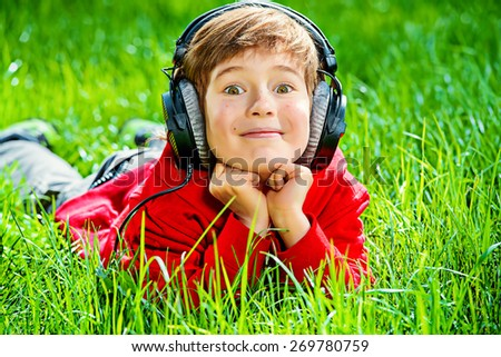 7 years old boy lying on a grass and listening to music in headphones. Summer day.  - stock photo