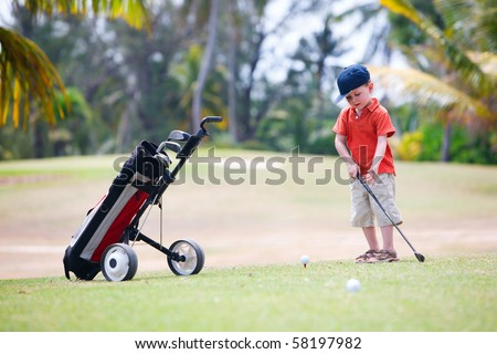 4 years old boy playing golf - stock photo