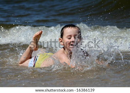 4 years old boy playing in the sea - stock photo