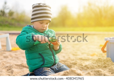2 years old boy playing outdoors in sandpit - stock photo