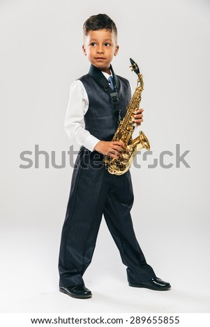 6 years old boy plays saxophone at studio - stock photo