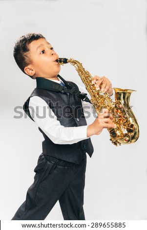 6 years old boy plays saxophone at studio, side view - stock photo