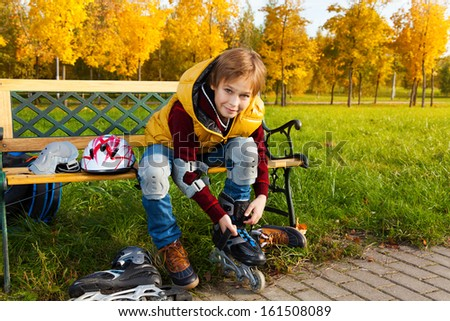 10 years old boy putting on roller blades sitting on the bench about to go skating