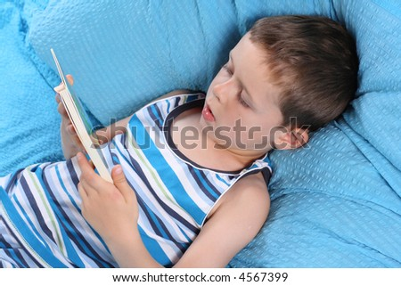 5-6 years old boy reading book in bed - relax