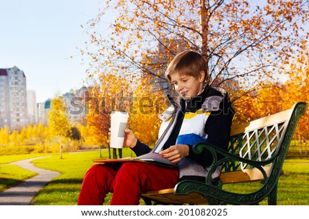 10 years old boy reading textbook and drinking coffee sitting on the bench in autumn park - stock photo