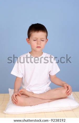 6 years old boy relaxing on blue background - stock photo