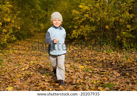 3 years old boy running in autumn scenery - stock photo