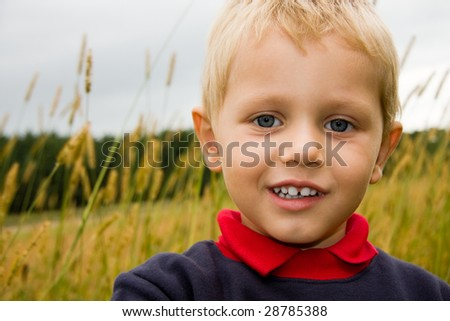 3 years old boy smiling on field outdoors - stock photo