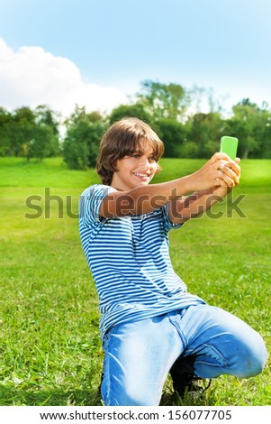 14 years old boy taking a picture of himself with camera on the cell phone in the park on sunny summer day - stock photo
