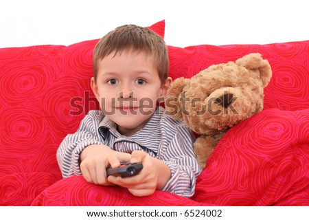 5-6 years old boy watching TV in bed - stock photo