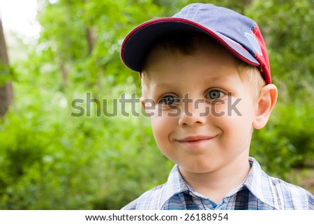 3 years old boy wearing cap outdoors. Spring portrait. - stock photo