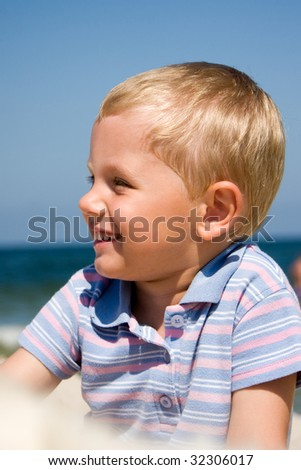 3 years old boy wearing casual clothes and smiling on a beach - stock photo