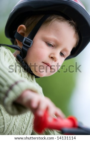 3 years old boy wearing safety bicycle helmet riding a bike
