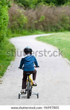 5 years old boy wearing safety bicycle helmet riding a bike - stock photo