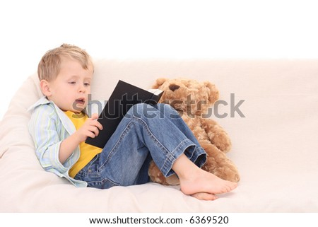 3-4 years old boy with book on the sofa - stock photo