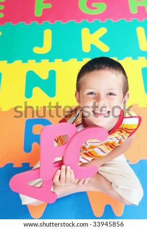 7 years old boy with colorful letters - schhol - stock photo