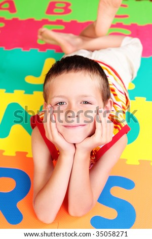 7 years old boy with colorful letters - school - stock photo