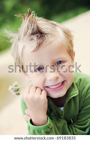 5 years old boy with flower outside - kids - stock photo