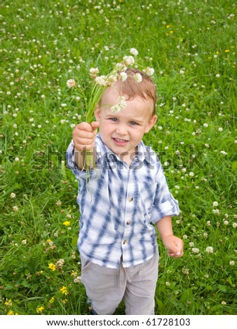 2 years old boy with flowers - stock photo