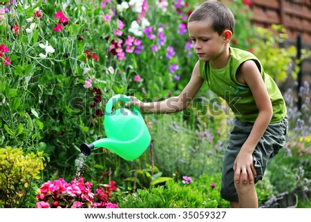 7 years old boy with watering can - kids - stock photo