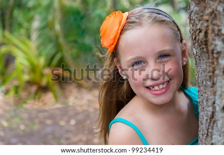 8 years old caucasian girl behind a tree in a backyard. - stock photo