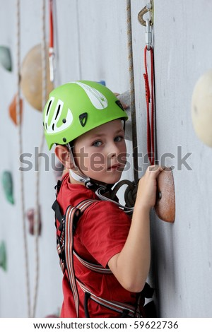 6 years old child climbing on a wall in a climbing center. - stock photo