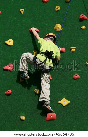5 years old child climbing on a wall in an outdoor climbing center - stock photo