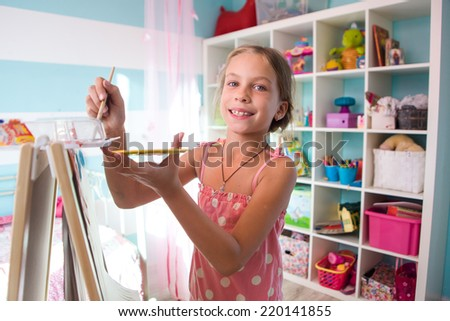 7-8 years old child drawing on easel in child room at home - stock photo
