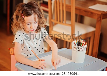 5 years old child girl drawing with pencils at home