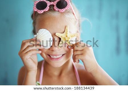 7 years old child holding seashell on blue background - stock photo