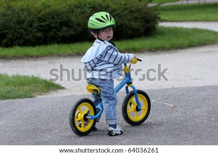 2 years old child learning to ride on his first bike - stock photo
