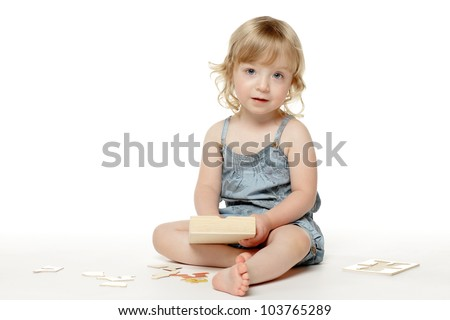 2 years old child sitting with a toy on the floor, over white - stock photo
