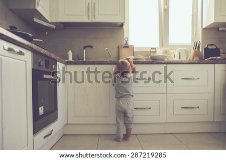 2 years old child standing on the floor alone in the kitchen, casual lifestyle photo series in real life interior - stock photo