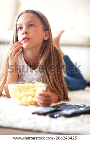 8 years old child watching tv laying down on a white carpet at home alone