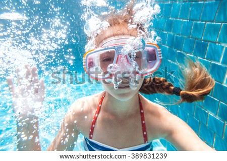 9 years old child wearing diving mask swimming in the pool, underwater shot - stock photo