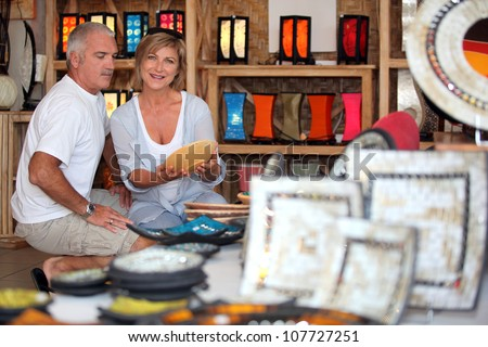 55 years old couple looking a plate in a handicrafts shop - stock photo