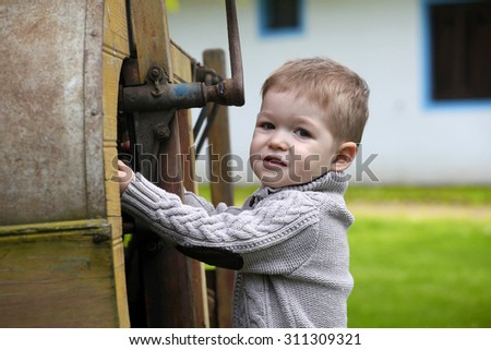2 years old curious Baby boy managing with old agricultural Machinery - stock photo