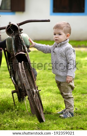 2 years old curious Baby boy walking around the old bike  - stock photo