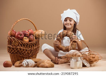 5 years old girl baker eating bakery products, studio shot - stock photo