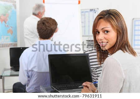 18 years old girl listening a teacher in a classroom - stock photo