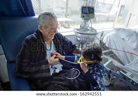 3 years old girl measuring heart beats to her 95 years old great grandfather.