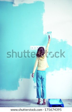 7 years old girl painting the wall at home, Instagram style toning - stock photo