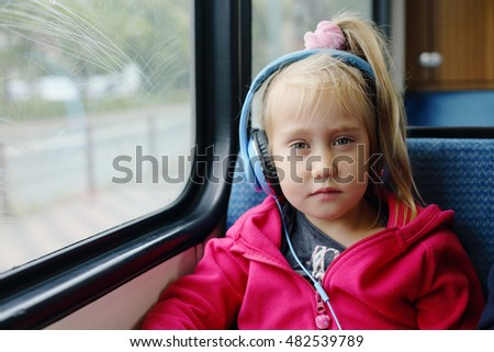 5 years old girl sitting in the train near the window