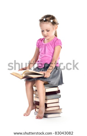 3 years old girl sitting on a cup of books and reading isolated on white - stock photo
